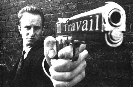 """Cette image en noir et blanc montre un  homme habille en costume cravate avec chemise blanche, a la coiffure impeccable, qui pointe un pistolet dans la direction du spectateur, l'ouverture du canon de l'arme apparaissant en gros au premier plan de l'image tandis que l'homme apparait au second plan. L'homme est en fait l'acteur Benoit Poelvoorde qui incarne un serial killer dans le film culte """"C'est arrive pres de chez vous"""" , un faux documentaire belge en noir et blanc de Remy Belvaux, Andre Bonzel et Benoît Poelvoorde sorti en 1992 qui met en scene une petite equipe de journalistes qui tournent un reportage sur Ben, un homme qui a la particularite de tuer pour gagner sa vie.  Il s'attaque surtout aux personnes de la classe moyenne et aux personnes agees, preferant, selon ses mots, """"travailler petit mais que ça rapporte beaucoup"""". On distingue sur le canon de l'arme le mot """"Travail"""" qui ne figure pas sur l'image originale puisqu'il est un ajour du Marginal Magnifique qui a choisi cette image pour illustrer son nouveau poeme """"Murderabilia"""" d'ores et deja culte, dans lequel il denonce une fois encore sa bete noire que represente le travail. L'image est particulierement bien choisie puisque le celebre poete compare le travail a un tueur et ses caracteristiques a des murderabilia qui sont les reliques ayant appartenues a des serial killer, objets donnant leur nom au poeme. Le poeme loi d'etre desespere est ausi amusant puisque Le Marginal Magnifique n'hesite pas a convoquer Nabilla et son celebre """"Allo quoi"""" pour figurer aux cotes d'images beaucoup plus sombres. Encore un immense poeme du Marginal Magnifique !!! Bravo !!!"""