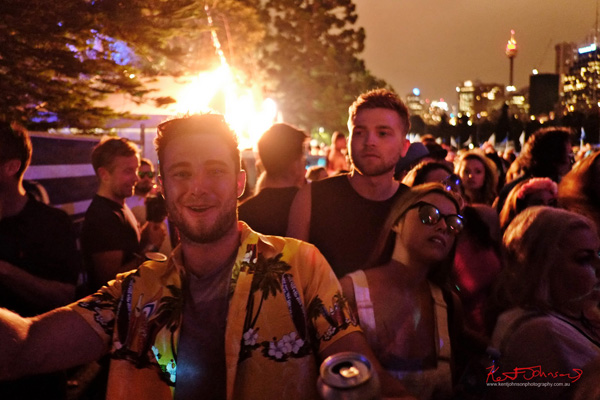 Revellers to the back of the lowerer festival area, Sydney cityscape at night in the background. Harbour Life Music Festival Sydney 2016. Photographed by Kent Johnson for Street Fashion Sydney.