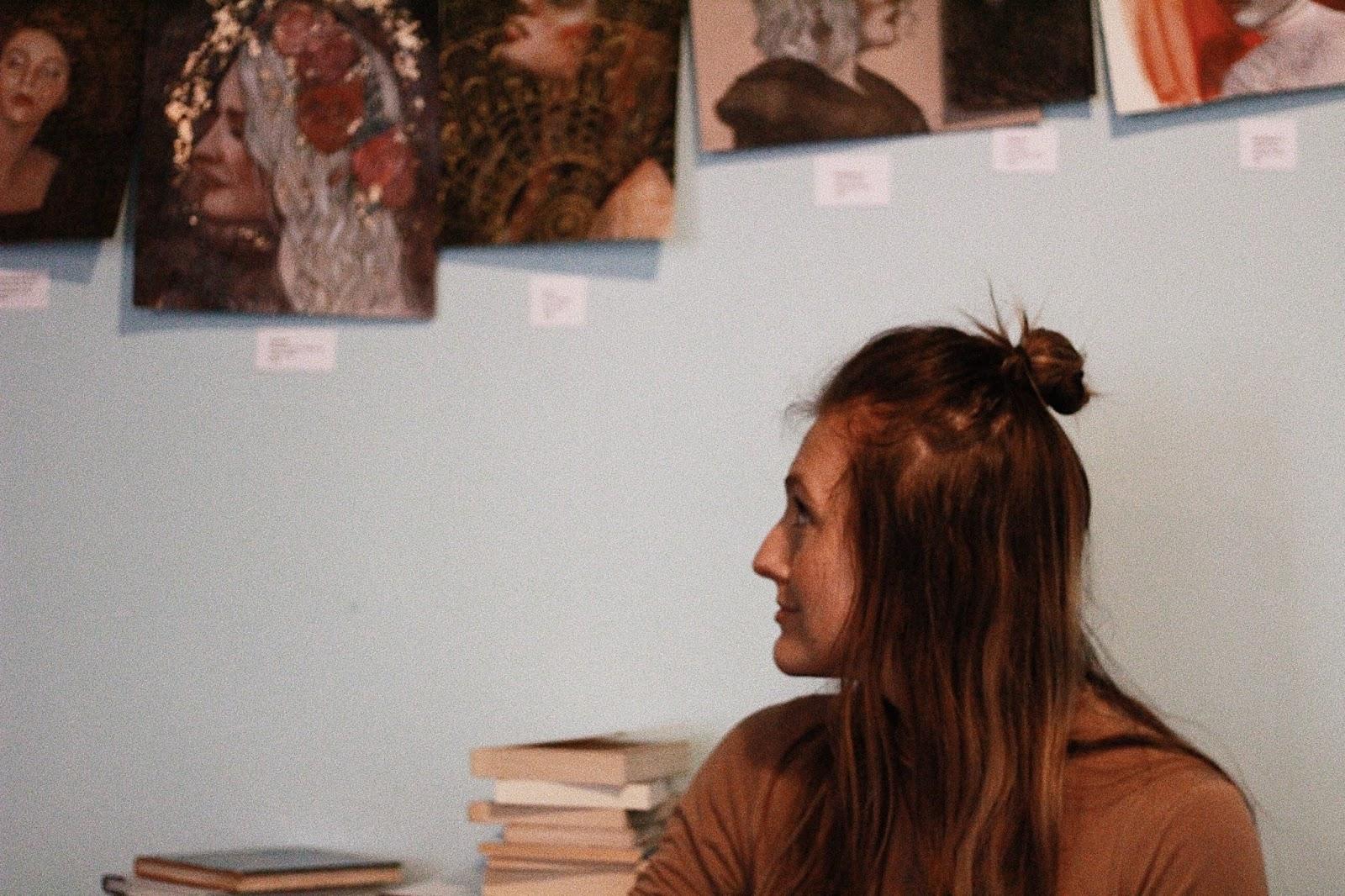 girl looking at paintings