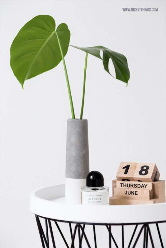 Nachttisch aus Ferm Living Wire Basket mit Hpuse Doctor Vase Wood Blocks Kalender und Monstera