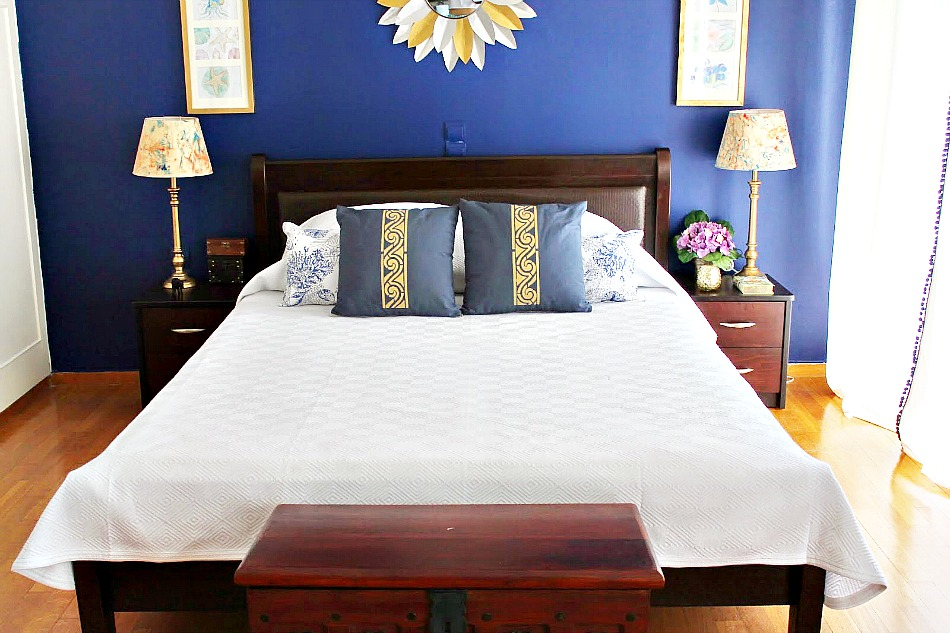 White duvet cover, blue pillows with gold stencil