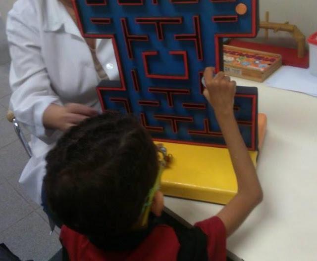 Foto mostrando o paciente testando o brinquedo criado pela equipe. O produto é uma tabuleiro vertical com o fundo azul e com detalhes em vermelho.