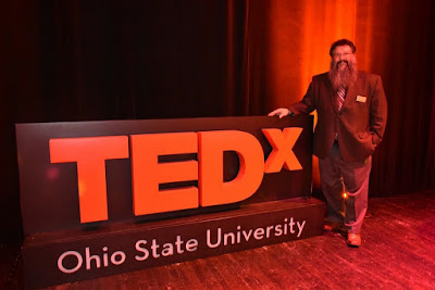 Dr. Michael Stamatikos standing next to the TEDxOhioStateUniversity sign on stage at the 2019 event. Image Courtesy of Dr. Stamatikos.