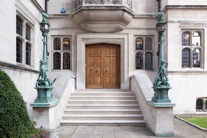 Stone stairs with two pillars leading up to a large double wooden door