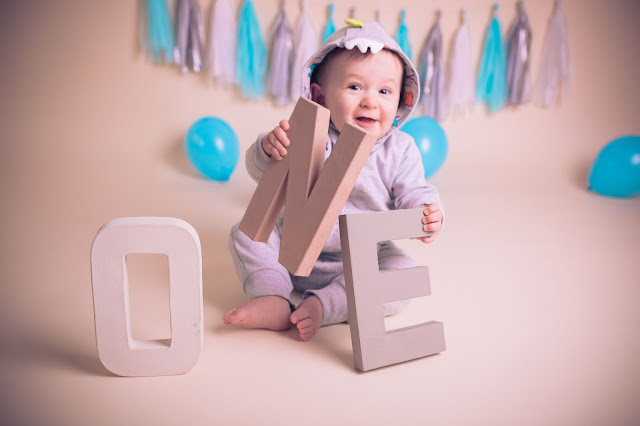 photo of baby holding a wooden letter N and smiling