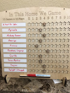 A wooden board, laser etched, with feet to allow it to stand up. Along the top it reads, 'In This Home We Game.' Beneath that it says '10 Games x 10 Plays,' next to the numbers zero through ten. The main portion of the board is ten strips of dry-erase areas on which are written the names of ten games. Beside these are rows of ten meeple-shaped cut-out spaces, with meeples placed in each row to indicate how many times that game has been played. There is a ledge at the bottom on which to place a dry-erase marker.