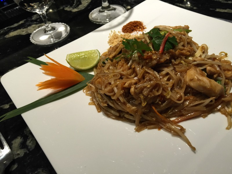 Chicken pad Thai with a tulip shaped carrot on the side