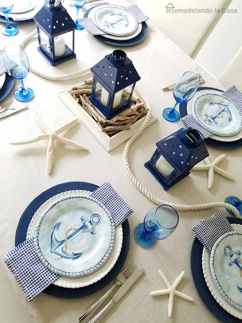 gingham napkins, anchor salad plates, starfish decor, blue lanterns and blue glasses on this coastal tablescape with jean chargers