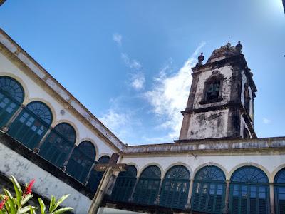 Fotografia colorida do interior do convento de São Francisco. Vistas duas alas do primeiro andara da edificação, com janelas em arco. Por trás, o alto da torre da Igreja, realçada pelo céu azul com algumas nuvens brancas.