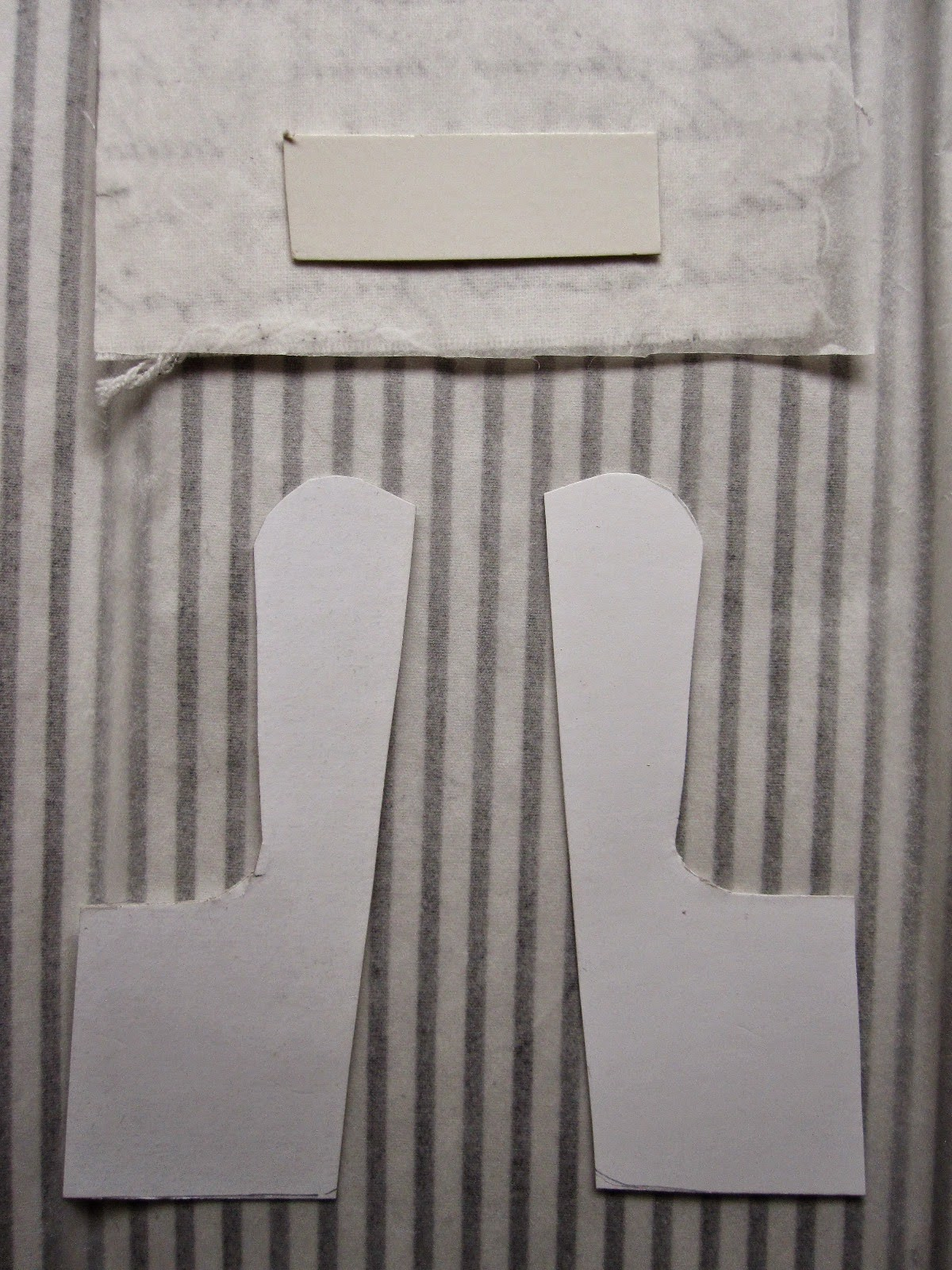 Two cardboard chair component shapes laid out on the wrong side of fabric, ready to be cut out.