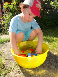 Big Boy playing with Lego Bricks in a bowl of water