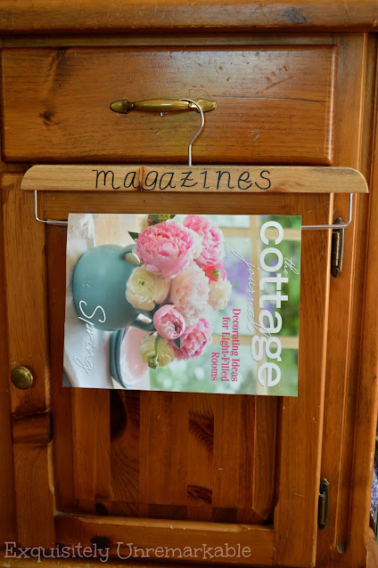 Magazine hanging on wooden hanger that has the word magazine labeled on it