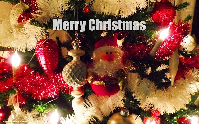 Kerstboom, brandende kerstverlichting, kerstman, kerstballen en rode en witte slingers
