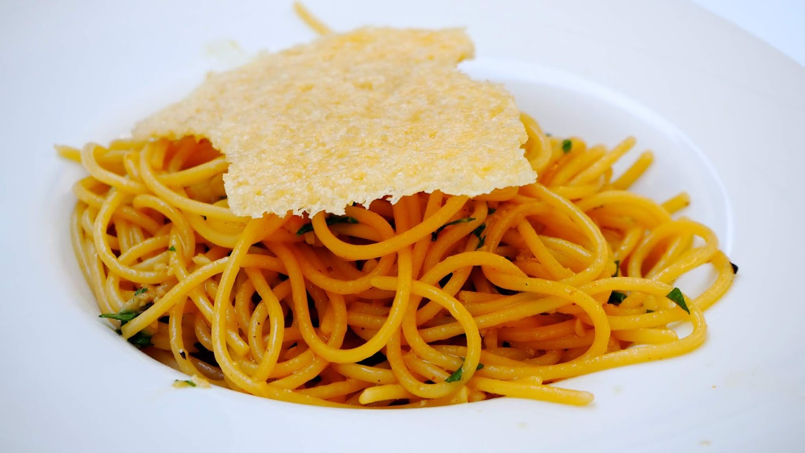 Spaghetti with chilli, garlic and olive oil topped with a parmesan crisp