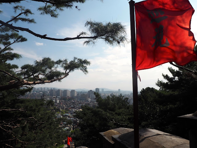 Red flags on Hwaseong Fortress walls and the view looking over Suwon, Gyeonggi-do, South Korea