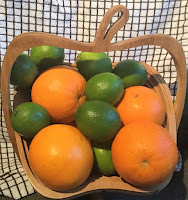 Wooden fruit bowl with oranges and limes