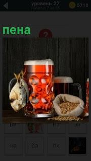 Стоит кружка пива с пеной на верху и рядом рыбка висит, мешочек с орешками открытый