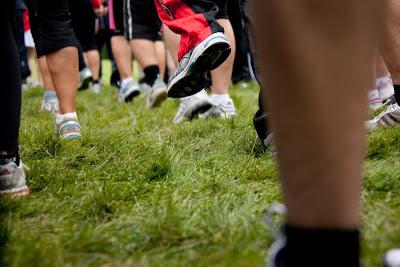 Grupp av löpare som på gräs, enbart ben och skor syns.