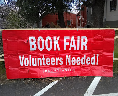 Banner with white letters against red background, reading: 'BOOK FAIR Volunteers Needed!,' attached to metal gate railing