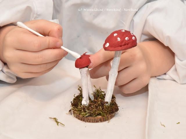 Herbstbasteln mit Kindern. Mit Naturmaterialien lassen sich viele tolle Kunstwerke gestalten! Diesmal entstand ein Fliegenpilz! Aus Walnussschalen, Eichelhütchen, Moos und Ästen.