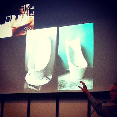 Mary Featherston giving a talk in front of a slide showing maquettes and tests of the Grant Featherston Talking Chair.