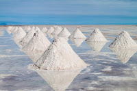 Hand-shoveled salt piles dry on Bolivia's Salar de Uyuni, thought to be one of the richest sources of lithium in the world. Solar evaporation takes up to 18 months. (Credit: Matyas Rehak, Shutterstock.com) Click to Enlarge.