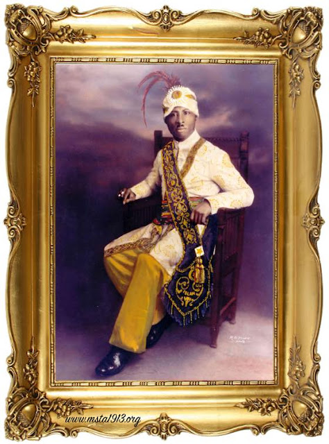 Extravagently framed portrait of Prophet Noble Drew Ali seated wearing a turban and feather with Moorish garb.