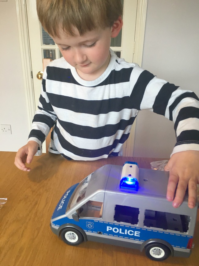 boy-playing-with-unfinished-Playmobil-police-van-with-lights-flashing