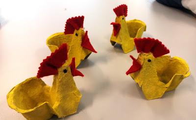 Quatro galinhas de cartão, amarelas com cristas vermelhas, pintadas e decoradas pelos alunos.