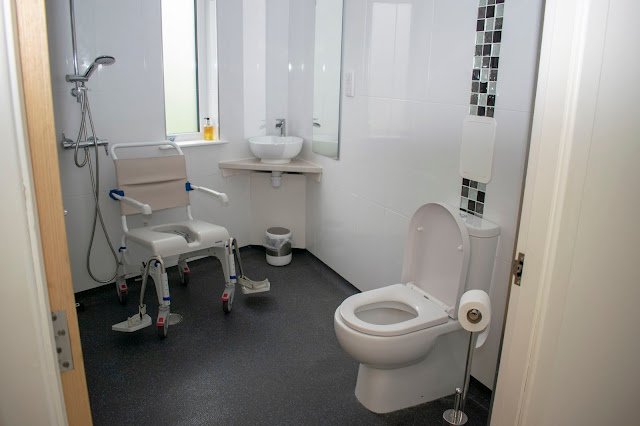 Large white and black wetroom with toilet, shower chair and shower