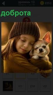Добрая девочка обнимает на руках собаку с закрытыми глазами, которая прижалась к голове и сложила лапки на руке