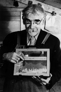 A black and white photograph of a man holding up an ant farm.