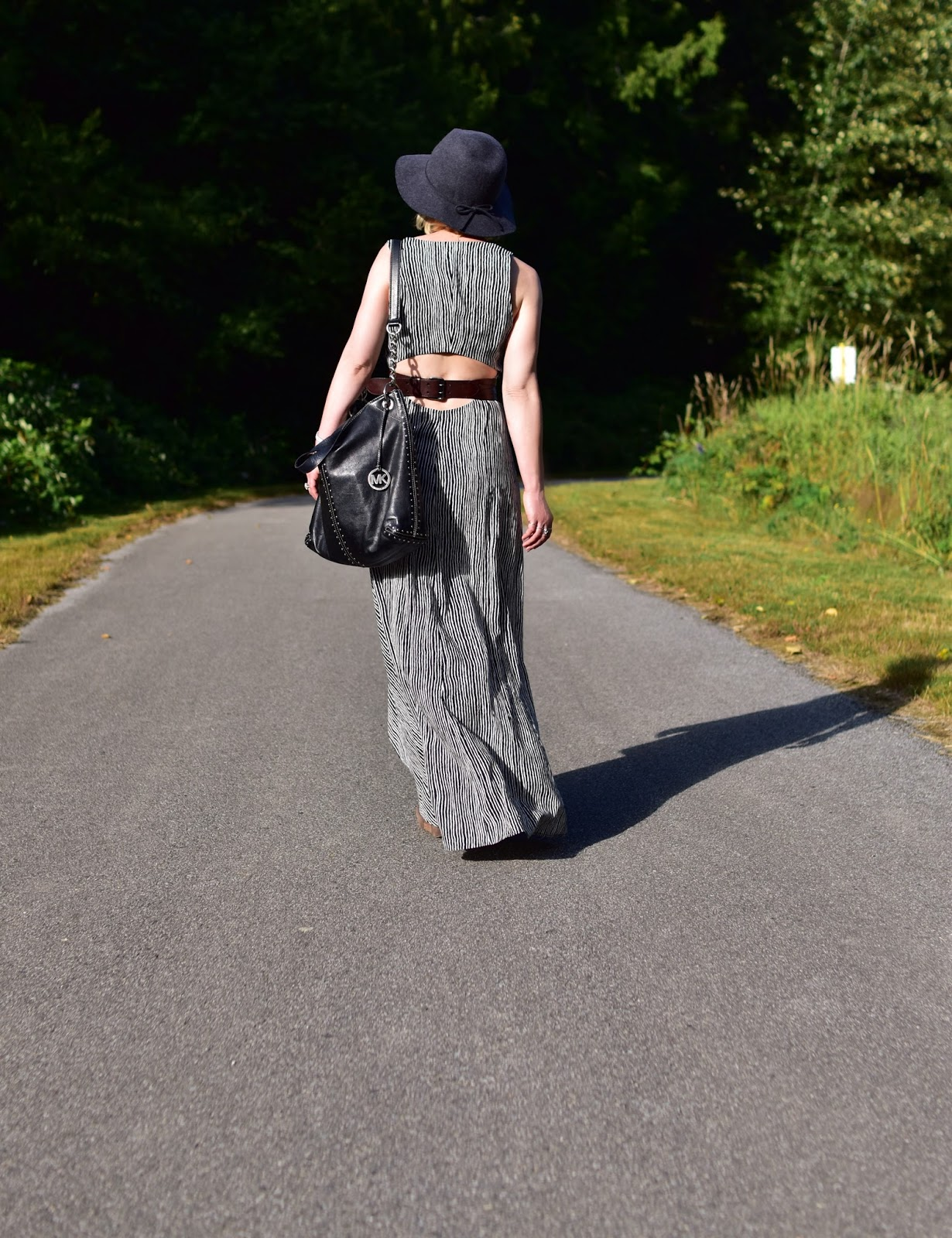 Monika Faulkner styles a striped maxi-dress with a corset belt, floppy hat, and MK bag