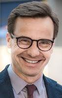 Bild på Sveriges stadsminister 2018-2022. Glasögon, slips, brunt hår och ett leende.