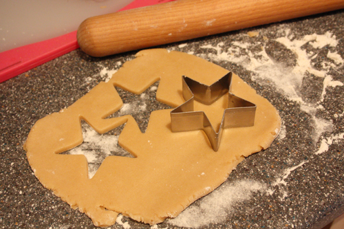 sugar cookie dough with a star cookie cutter, and some stars cut out of the rolled out dough