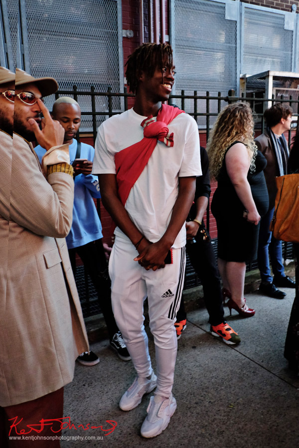 man in white tee, adidas pans and shoes with red jacket tied diagonally across his chest. Street Fashion Sydney - New York Edition photographed by Kent Johnson