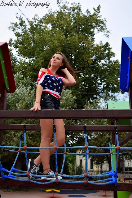 22.08.2015 Bluzka flaga amerykańska opadające ramię, czarne trampki wężowa skórka, czarne spodenki z brokatem, Sesja na placu zabaw w Mielcu