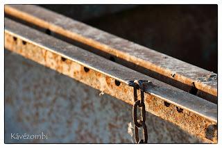 Rozsdás fémből kilógó lánc