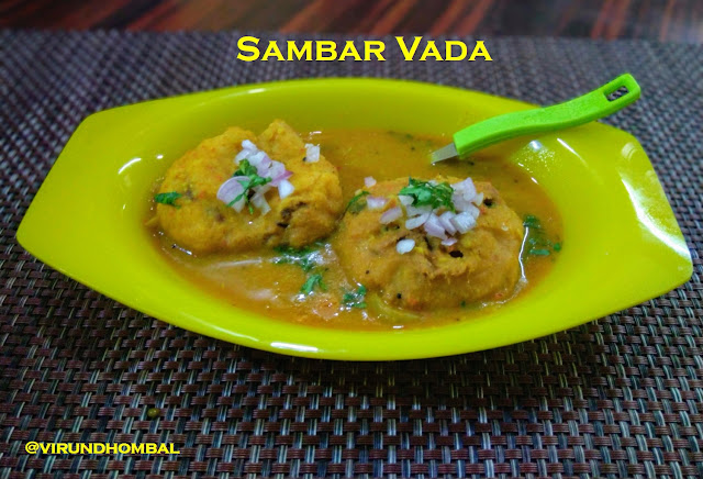 Sambar Vada -  easy and tasty  homemade sambar vada with simple cooking methods. The recipe for the sambar is same as the tiffin sambar recipe posted early this year. The only change in the tiffin sambar recipe is that I have added toor dal instead of moong dal because moong dal will be thick for sambar vada. The fried medhu vadas are soaked in the warm water for 10 minutes and then added in the hot sambar. The tiffin sambar can be made ahead of time and refrigerated. Just warm the sambar in a broad pan or kadai to soak the vadas. For vadas I have added few onions and green chillies. Just before serving, a handful of finely chopped onions are garnished on the top of the sambar vadas.