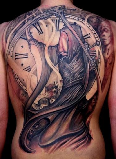 Um rosto Grim Reaper tatuagem. Sobre essa tatuagem, o Grim Reaper é visto estar segurando a foice pelo lado enquanto segurando um relógio no plano de fundo. O rosto é coberto com algum tipo de pano.