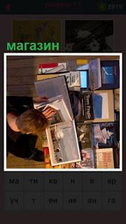 читатель в магазине рассматривает буклеты и книги