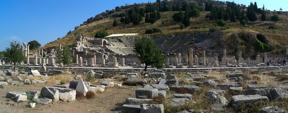 Une vue panoramique de l'agora supérieure, vaste place qui desservait les bâtiments administratifs : on aperçoit le mieux conservé d'entre eux, l'Odéon. A gauche, le prytanée.