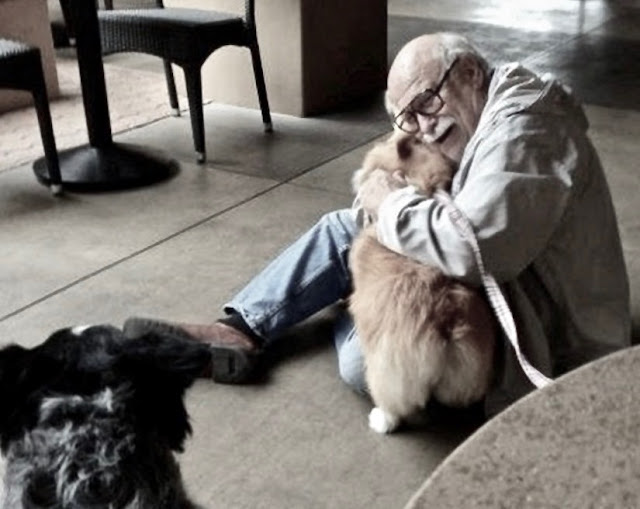 A senior sits on the floor, hugging  a therapy dog. Gratitude and other stories of giving thanks. marchmatron.com