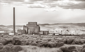 1940s-era nuclear reactor with smokestack, surrounded by shrubbs and hills.