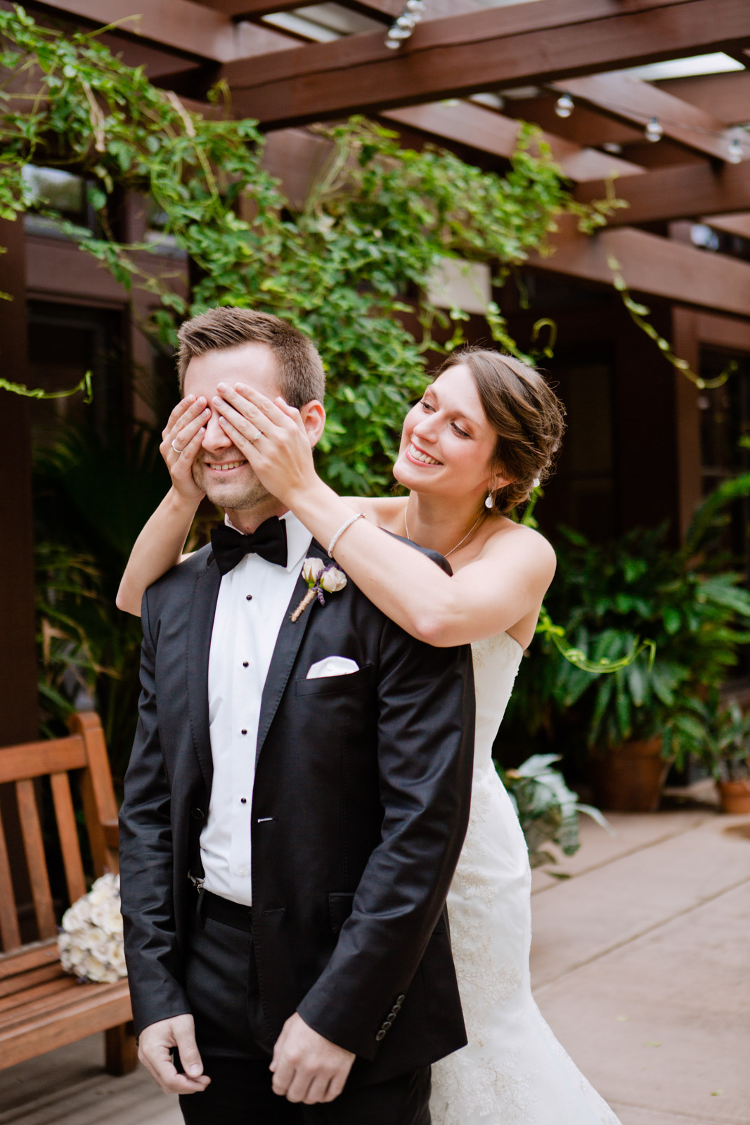 a bride covers her grooms eyes before he sets eyes on her for the first look