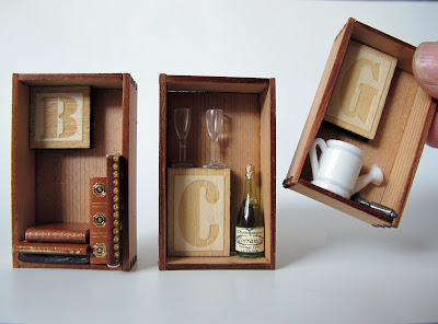 Three miniature cedar crates containing letters of the alphabet and items that match. From left to right: 'B' and five miniature books, 'C' and a bottle of champagne with two glasses, and 'G' with a watering can and trowel. A finger is shown for scale.