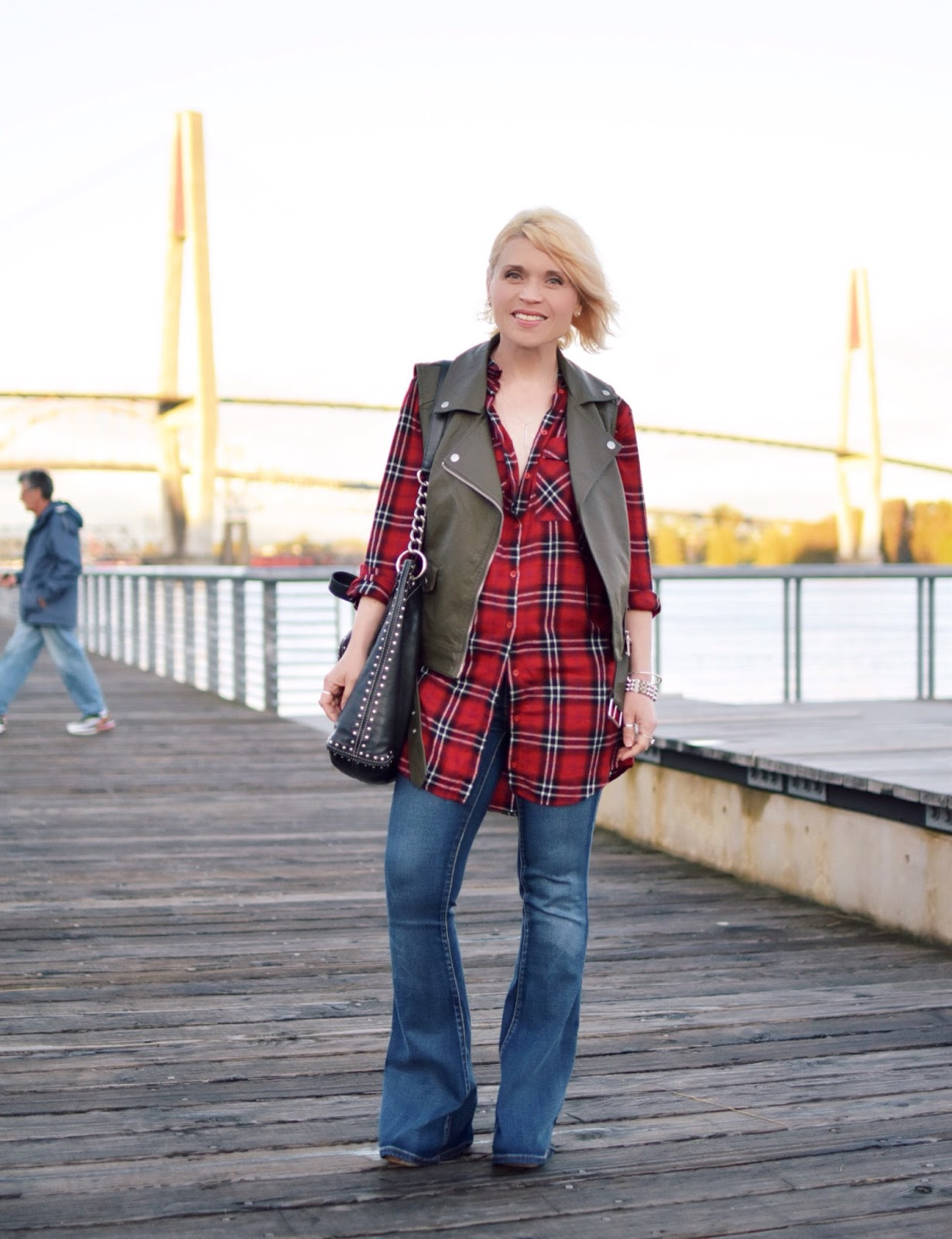 Monika Faulkner styles a red plaid tunic with flare jeans and an olive moto vest
