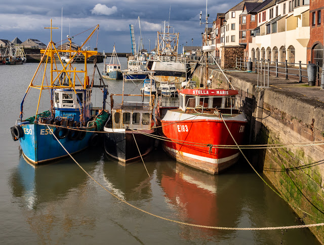 Photo of a closer view of some colourful fishing boats in the harbour