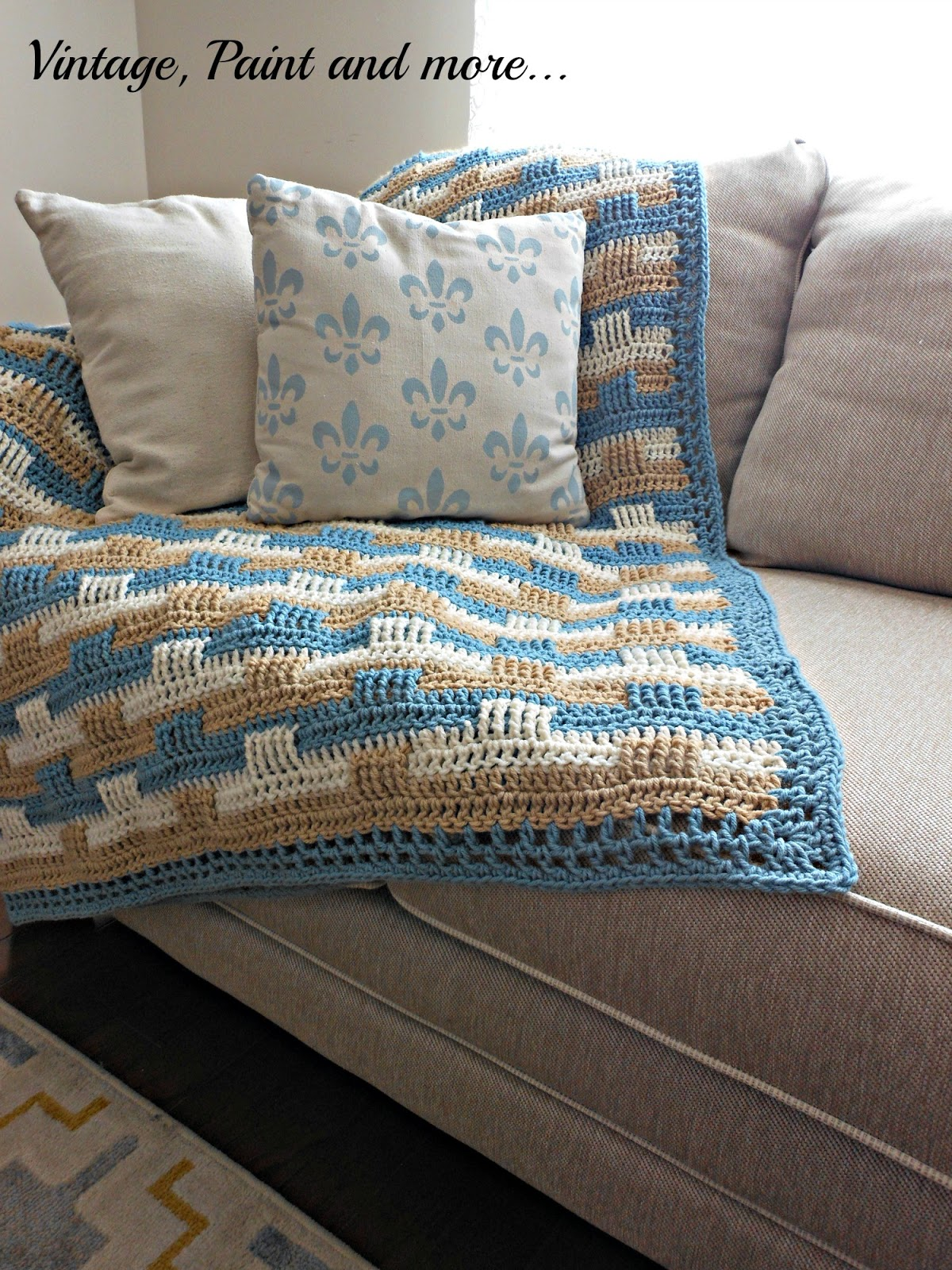 a crochet afghan using a basket weave pattern and DIY drop cloth pillow stenciled with craft paint
