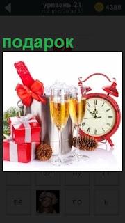 Будильник, шампанское в рюмках, кедровые шишки и подарок в коробке перевязанный белыми лентами